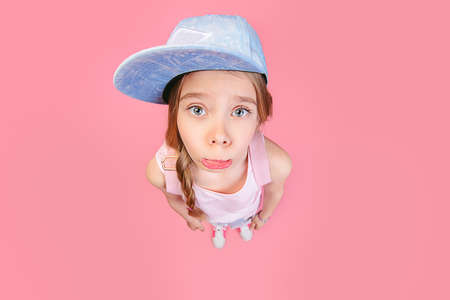 Close-up portrait of a funny emotional girl making faces at camera. Studio shot over pink background. Stock Photo