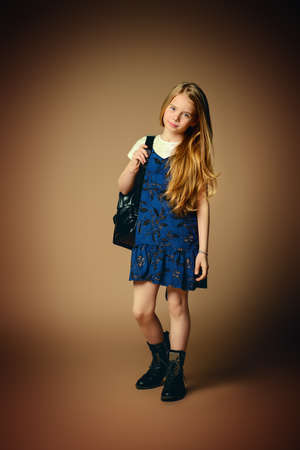 Childrens fashion. Cute eight year old girl with long blonde hair posing in summer dress and a bag. Studio shot. Full length portrait. Reklamní fotografie
