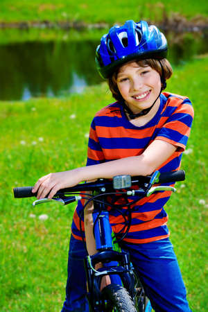 Cute cheerful boy is riding his bike. Happy summer holidays. Reklamní fotografie