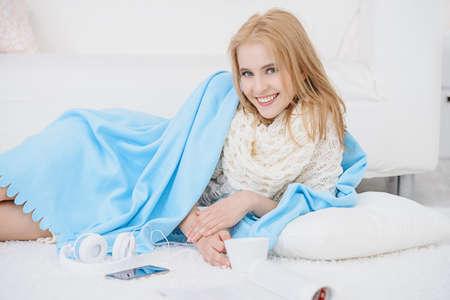 De gelukkige jonge vrouw geniet thuis van haar weekend. Luisteren naar muziek, smartphone gebruiken en tijdschriften lezen. Stockfoto