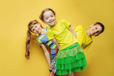 Happy joyful children having fun together. Children's fashion. Education. Happiness, activity and child concept. Bright yellow background. Archivio Fotografico