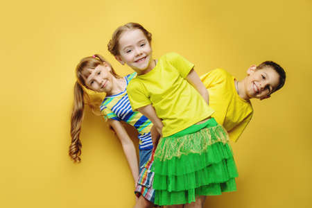 Happy joyful children having fun together. Children's fashion. Education. Happiness, activity and child concept. Bright yellow background. 免版税图像