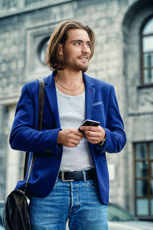 通りを歩きながら、彼のスマート フォンを使用して青年実業家。活気のあるアクティブなライフ スタイル。