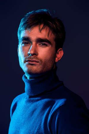 Porträt eines gutaussehenden Mannes mit Borste im blauen und roten Licht. Männliche Schönheit, Mode.