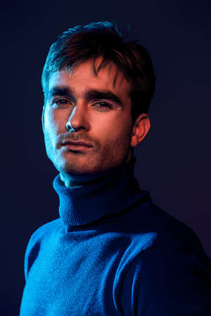 Portrait of a handsome man with bristle in blue and red light. Male beauty, fashion. Zdjęcie Seryjne