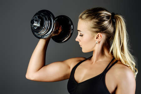 Beautiful athletic woman doing exercises with dumbbells. Fitness, bodybuilding. Health care. 版權商用圖片 - 84110439