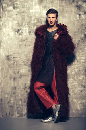 유행 쐈어. 긴 빨간 모피 코트에서 포즈 잘 생긴 남자 모델입니다. 남자의 아름다움, 패션. 스튜디오 촬영. 스톡 콘텐츠