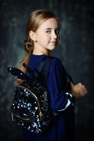 Portrait of a cute ten-year-old girl smiling at camera. Childrens fashion.