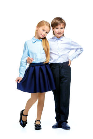 School fashion. Two cute children in school uniform posing at studio. Isolated over white background. Copy space. Full length portrait. Stock Photo