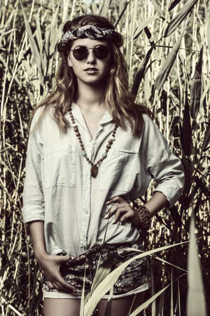 Beautiful hippie girl stands among the reeds. Fashion shot. Bohemian, bo-ho style. Sepia portrait. Stok Fotoğraf
