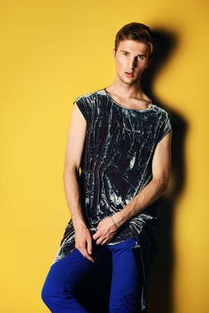 노란색 배경 위에 포즈 디자이너 옷 컬렉션에서 포즈 잘 생긴 남자 모델의 패션 쐈 어. 남자의 아름다움. 스톡 콘텐츠