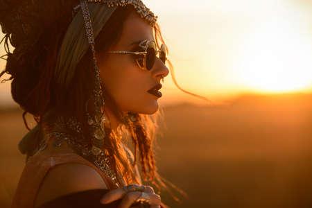 夕日の光線で自由奔放に生きる風衣装でポーズをとって壮大なファッションの女性。アウトドアファッション。ジプシー スタイル。