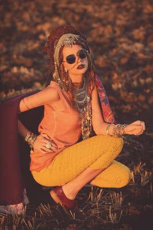 Stijlvolle boho vrouw in etnische sieraden en sjaal poseren op zonsondergang. Stockfoto