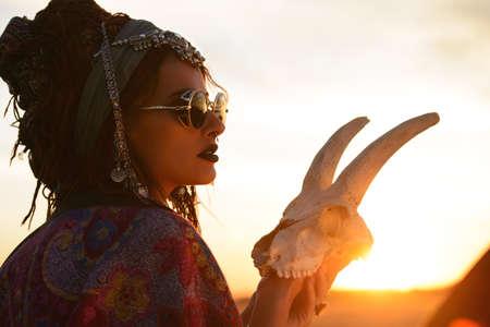 Prachtige gypsy fortuin teller met een schedel in de stralen van de zonsondergang. Stockfoto