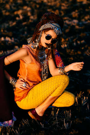 Stylish boho woman in ethnic jewelry and shawl posing on sunset.