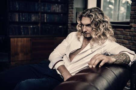 ソファーに横になっている白いシャツでハンサムなセクシーな若い男。男性の美容、ファッション。髪の毛、ヘアスタイル。 写真素材
