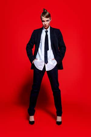 남자의 양복에서 포즈를 취하는 사치스러운 젊은 여자의 전체 길이 초상화. 남자의 스타일 의류. 빨간색 배경입니다. 패션 쐈어. 스톡 콘텐츠 - 85044953