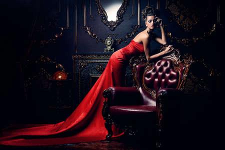 고급스러운 빨간 드레스와 고급 아파트에서 포즈 귀중 한 보석에 웅장 한 젊은 여자. 클래식 빈티지 인테리어입니다. 아름다움, 패션.