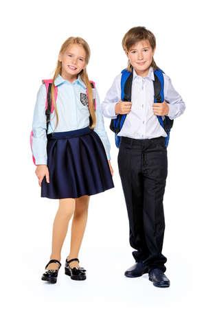 学校のファッション。2 人のかわいい子供学校制服とランドセル スタジオでポーズします。白い背景に分離されました。領域をコピーします。完全