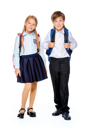 School fashion. Two cute children in school uniform and with school backpacks posing at studio. Isolated over white background. Copy space. Full length portrait.