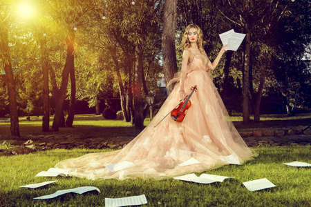 Beautiful fairy girl with the violin and sheets music on a sunny glade in the park. Musical concept. Classical music, violin. Фото со стока - 85191997