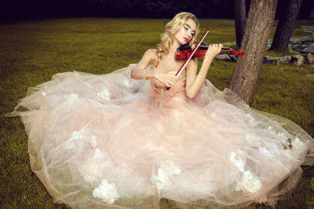 Beautiful fairy girl playing the violin on a sunny glade in the park. Musical concept. Classical music, violin. Imagens