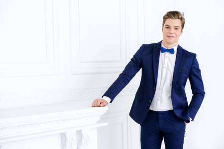 Handsome young man in elegant suit posing in luxurious apartments. Male beauty, fashion. Stock Photo