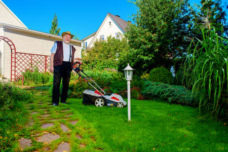 Happy retired senior man mows a lawn in his garden with a lawnmower. Stock Photo