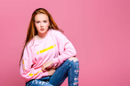 da4d8d912c63 Teen style. Beautiful young model with long hair posing at studio in jeans  and pink
