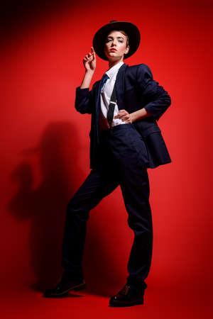 男のスーツと帽子でポーズ、魅力的な若い女性の完全な長さの肖像画。男のスタイルの服。背景が赤です。ファッションを撮影しました。