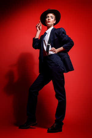 Full length portrait of an attractive young woman posing in a mans suit and a hat. Mans style clothing. Red background. Fashion shot.