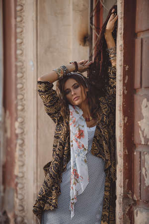 Female style. Feminine fashion model posing in boho style clothes on a street. Outdoor fashion. 免版税图像