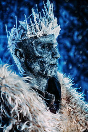 Close-up portrait of The King zombie warrior in the armor of a medieval knight covered with snow. Halloween. Horror fantasy film. Stock Photo
