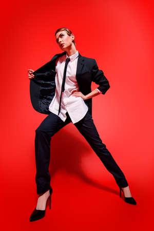 남자의 양복에서 포즈를 취하는 사치스러운 젊은 여자의 전체 길이 초상화. 남자의 스타일 의류. 빨간색 배경입니다. 패션 쐈어. 스톡 콘텐츠 - 85323311