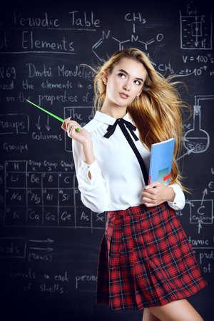 칠판 배경 위에 학교 옷을 입고 긴 금발 머리 가진 아름다운 학생 소녀.