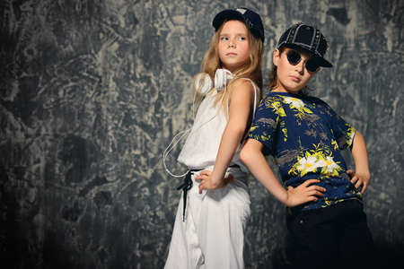 Two cool modern kids posing together in hip-hop style clothes. Childrens fashion. Zdjęcie Seryjne