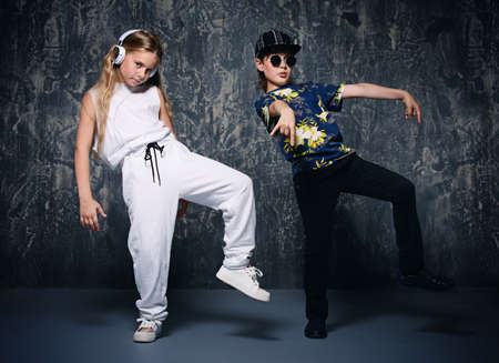 Two cool modern kids posing together in hip-hop style clothes. Childrens fashion. Фото со стока
