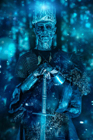 The king of the dead warriors in knightly armor stands in the night forest. Fantasy horror film. Halloween. Zombie.