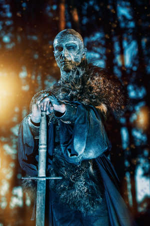 Zombie warrior in knightly armor stands in the night forest.