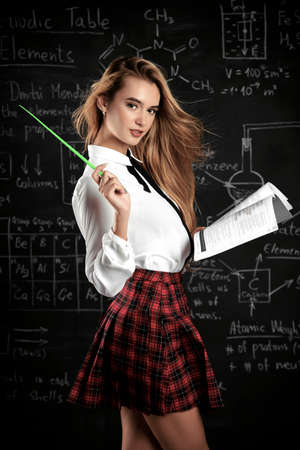 Beautiful student girl with long blonde hair posing in school clothes over blackboard background.