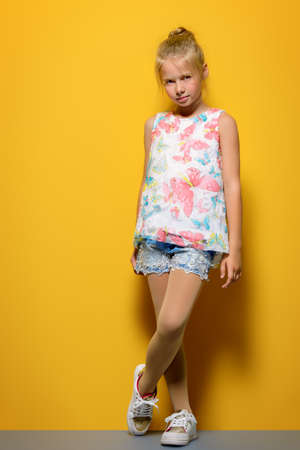 Bright summer girl. Cute eight-year-old girl in summer clothes posing over yellow background. 版權商用圖片