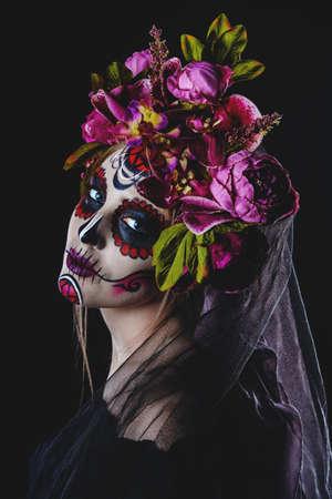 Portrait of a girl with sugar skull makeup over black background. Calavera Catrina. Dia de los muertos. Day of The Dead. Halloween.