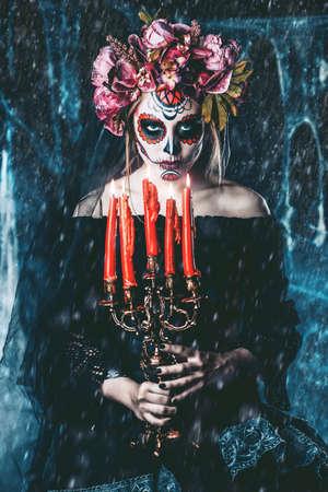 カラベラ カトリーナ暗い怖い背景の上のろうそくを保持しています。砂糖頭蓋骨化粧。Dia デ ロス ムエルトス。死者の日。ハロウィーン。