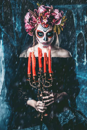 Calavera Catrina holding candles over dark scary background. Sugar skull makeup. Dia de los muertos. Day of The Dead. Halloween.