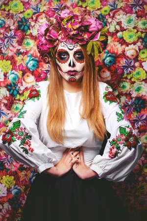 Dia de los muertos. Dia de los Muertos. Mujer con maquillaje de calavera de azúcar sobre un fondo floral. Calavera Catrina. Festividad de Todos los Santos. Foto de archivo - 85948835