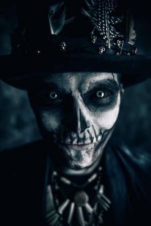 Close-up portrait of a man with a skull makeup dressed in a tail-coat and a top-hat. Baron Saturday. Baron Samedi. Dia de los muertos. Day of The Dead. Halloween. Stock Photo - 85979130