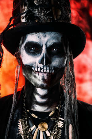 A man with a skull makeup dressed in a tail-coat and a top-hat. Baron Saturday. Baron Samedi. Dia de los muertos. Day of The Dead. Halloween. Stock Photo - 85979139