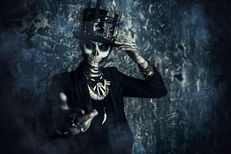Close-up portrait of a man with a skull makeup dressed in a tail-coat and a top-hat. Baron Saturday. Baron Samedi. Dia de los muertos. Day of The Dead. Halloween. 版權商用圖片 - 85979146