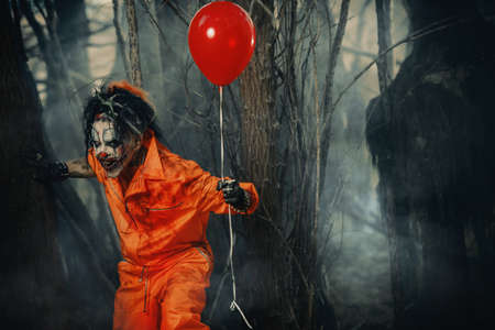 Scary man clown stained in blood in a night forest with a balloon. Male zombie clown. Halloween. Horror. 스톡 콘텐츠