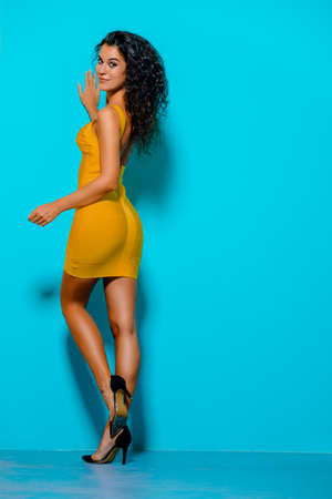 Beauty, fashion shot. Beautiful slender tanned girl in a yellow dress on a blue background. Brunette hair.